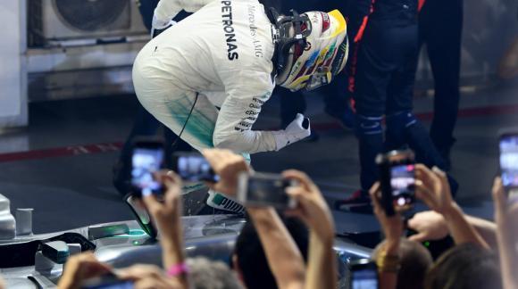 Hamilton festeja arriba de su Mercedes la victoria en Singapur