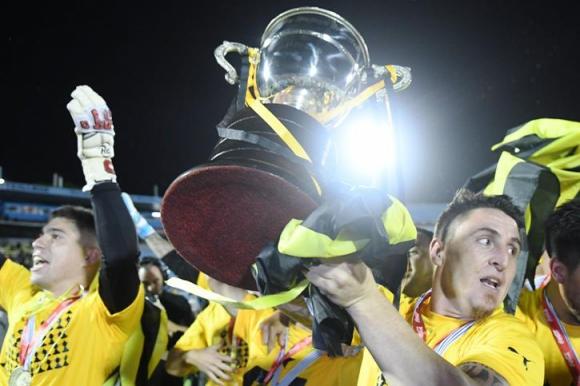 """El """"Cebolla"""" Rodríguez, capitán y símbolo del Peñarol 2017, con la copa de campeón. Foto: Ariel Colmegna"""