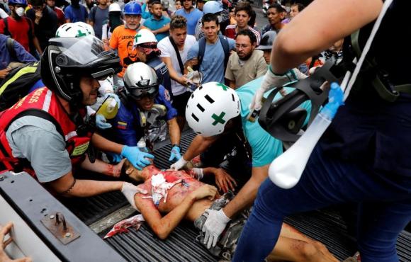 Servicios médicos asisten a un joven gravemente herido durante las protestas. Foto: Reuters