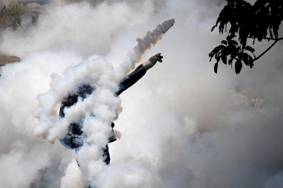 Manifestante devuelve un gas lacrimógeno arrojado por la Policía. Foto: Reuters.