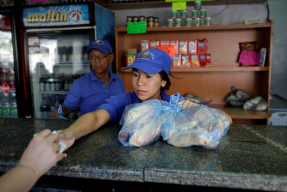 La empleada de una tienda vende pan en Caracas. FOTO: Reuters