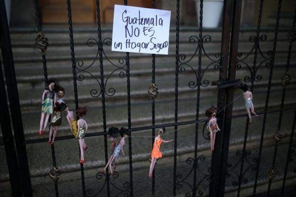 Manifestantes cuelgan muñecas quemadas enfrente a la Casa Presidencial. Foto: EFE