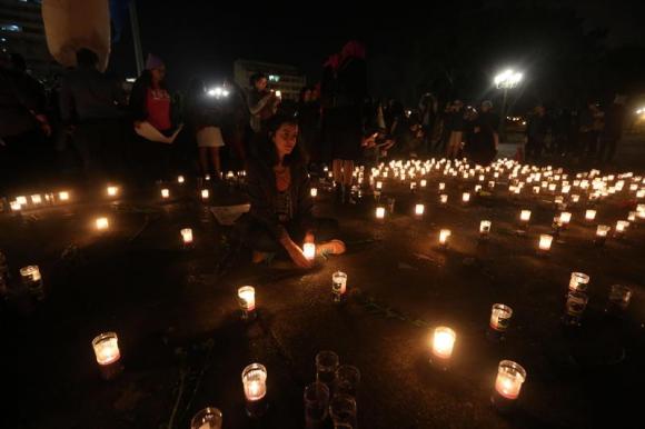 Integrantes de la fundación Sobrevivientes encienden velas en honor a las víctimas. Foto: EFE