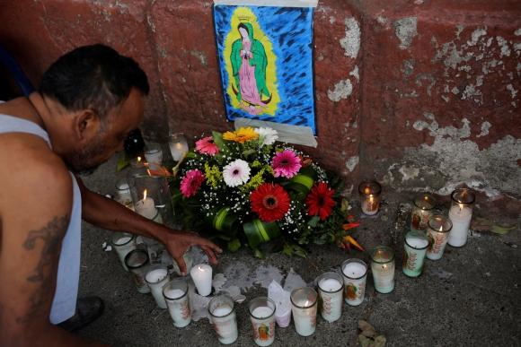 Familiares prenden velas afuera de la morgue. Foto: Reuters