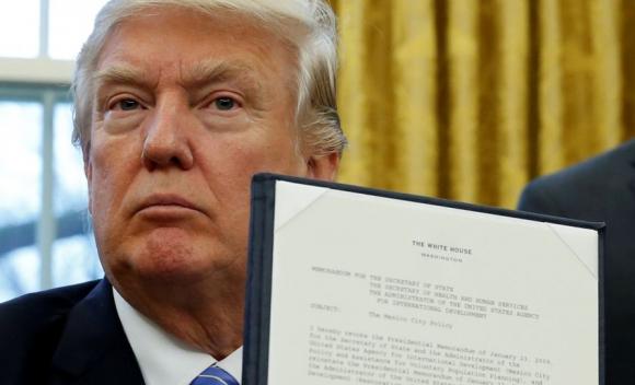 Trump muestra el decreto que ordena la salda del TPP. Foto: Reuters