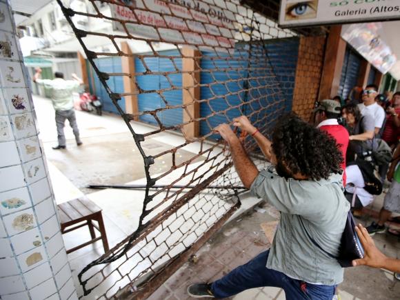 Personas intentan entrar a la fuerza en un shopping de la ciudad. Foto: Reuters