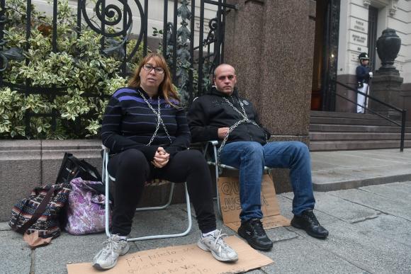 Huelga: Fabián y Estela encadenados en la puerta de la SCJ. Foto: A. Colmegna