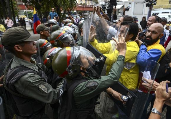 Incidentes: diputados de la oposición forcejeando con efectivos de la policía. Foto: AFP