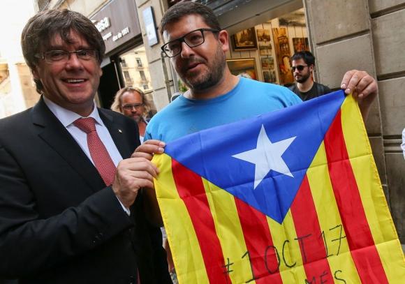 Puigdemont: el presidente catalán junto a un partidario del referéndum. Foto: Reuters
