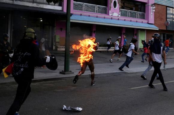 Un joven fue agredido y prendido fuego en medio de una manifestación. Foto: Reuters