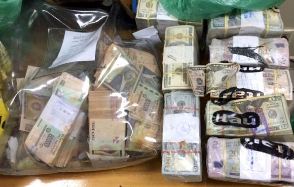 Botín: parte del dinero recuperado del asalto, junto a armas y vehículos. Foto: AFP