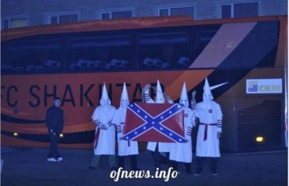 Aficionados del Dynamo posan con ropa del Ku Klux Kan frente al bus del Shakhtar