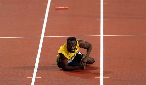 Usain Bolt en el piso tras lesionarse en su última carrera. Foto: EFE