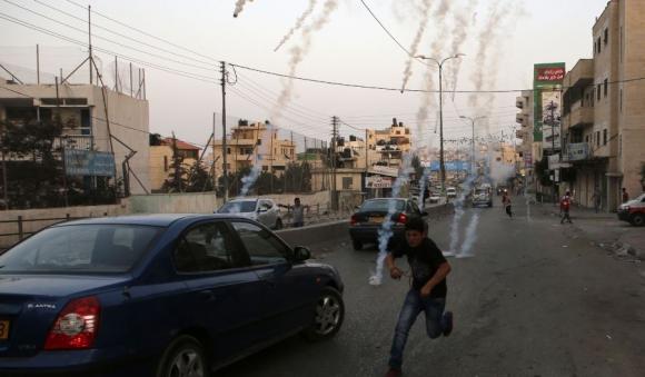 Un palestino se cubre de los gases lacrimógenos que lanzó el Ejército. Foto: AFP