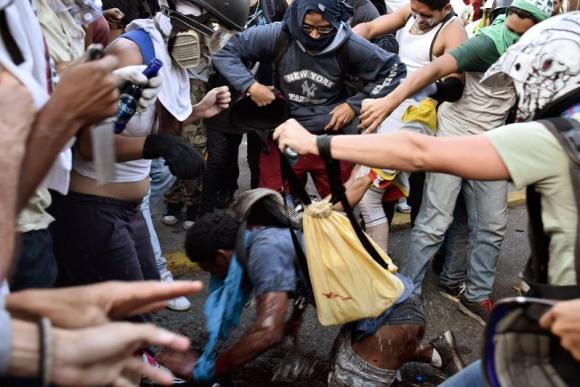 El joven es golpeado y rociado con una sustancia inflamable. Foto: AFP.