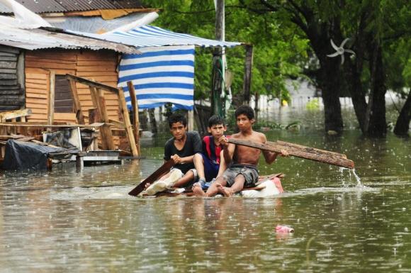 Tres adolescentes intentan navegar en Paysandú, tras inundación a fines de 2015. Foto: Fernando Ponzetto