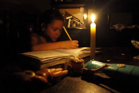 Una niña hace su tarea a la luz de las velas durante un corte en San Cristobal. Foto: Reuters