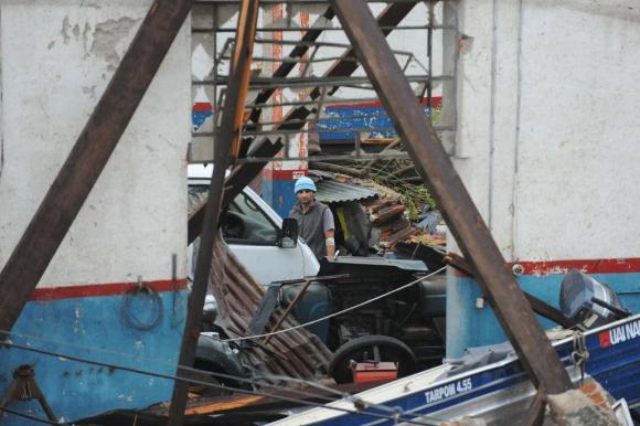 Un trabajador vuelve al galpón destruido. Foto: Fernando Ponzetto
