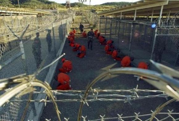 Detenidos se sientan en área de espera. Foto: Reuters