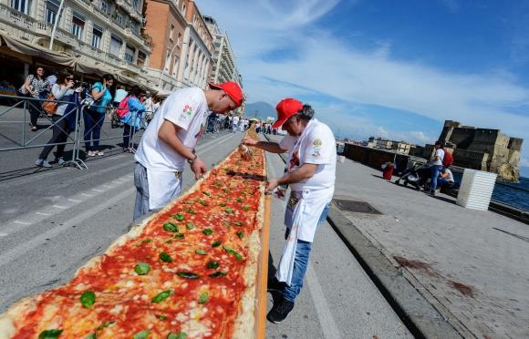 Cocineros preparan la pizza más larga del mundo. Foto: AFP