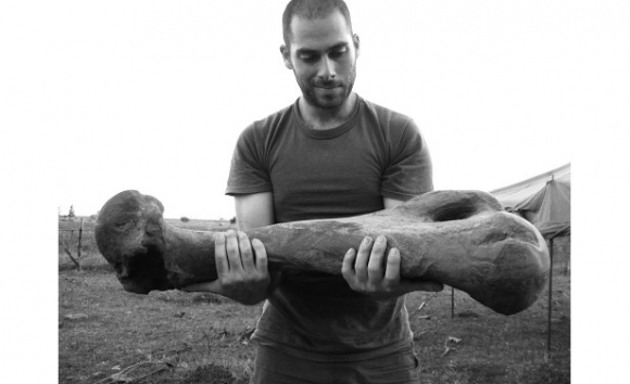 Sebastián Tambusso sostiene el gran fémur del perezoso gigante Lestodón