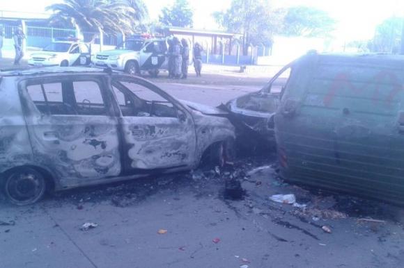 Vehículos incendiados en barrio Marconi. Detrás, la Guardia Republicana. Foto: Gabriel Rodríguez.