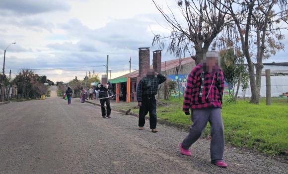 Pacientes caminan por Ituzaingó, donde viven en casas particulares. Foto: El País
