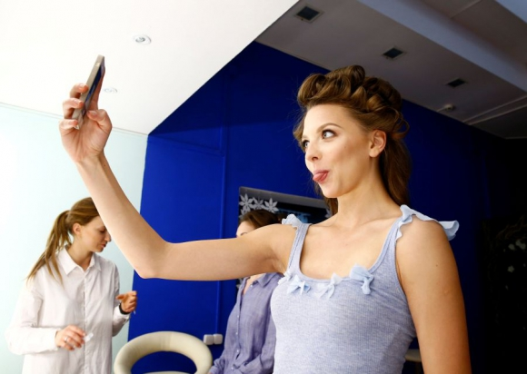 Melitina Staniouta se saca una selfie mientras la maquillan. Foto Reuters
