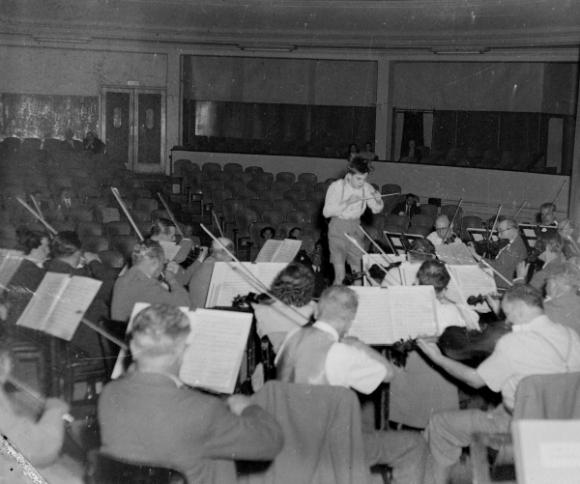 El niño prodigio Pierino Gamba dirige una orquesta.