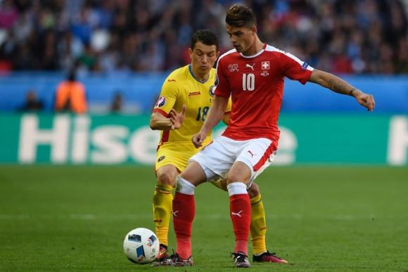 El suizo, Xhaka, y el rumano Prepelita disputando el balón. Foto: AFP