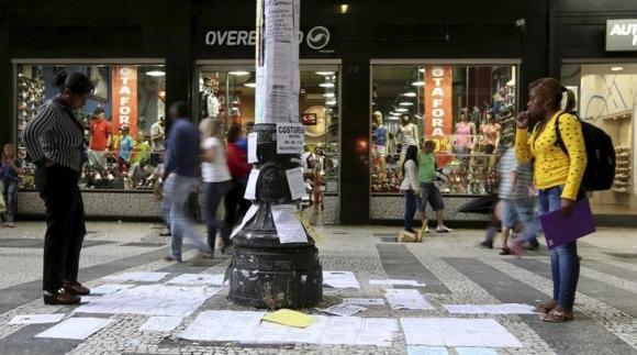 Transeúntes observan avisos de empleo en San Pablo. Foto: Reuters