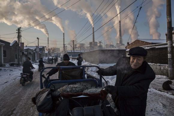 Primer premio en Vida Cotidiana del WPP. Un hombre chino empuja su triciclo rumbo a la planta de carbón en Shanxi, China. Noviembre 2015. La imagen pertenece al fotógrafo Kevin Frayer. Foto: vía a Reuters.