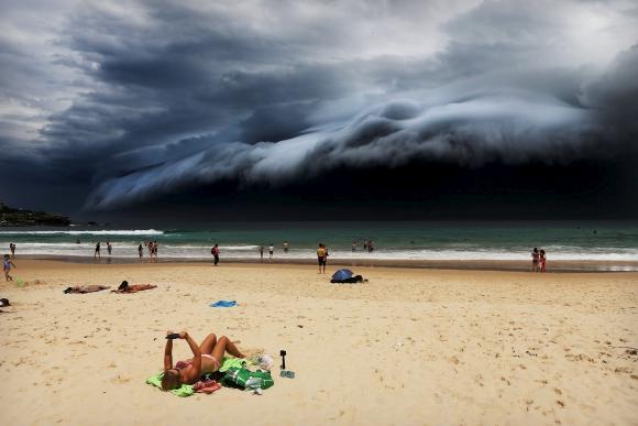 Primer premio en Naturaleza del WPP. Un bañista en Bondi Beach, Sydney no repara en la llegada de un tsunami y tormenta. La imagen pertenece al fotógrafo Rohan Kelly. Foto: vía Reuters