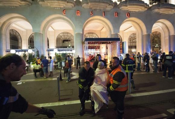 Emergencia: Agentes de seguridad trasladan a mujer herida. Foto: EFE