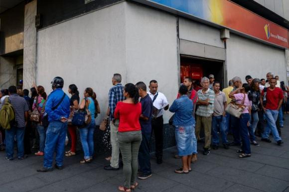 Colas en los bancos para deshacerse de los billetes de 100 bolívares. Foto: AFP.