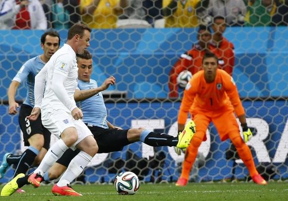 José María Giménez marca a Wayne Rooney en su debut Mundial. Foto: Reuters