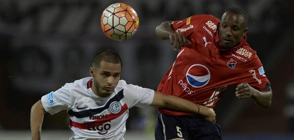 Josue Colman disputa por la pelota ante Juan Valencia. Foto: AFP