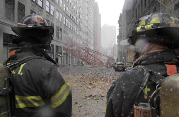Bomberos trabajan en calle donde cayó la grúa. Foto: Reuters