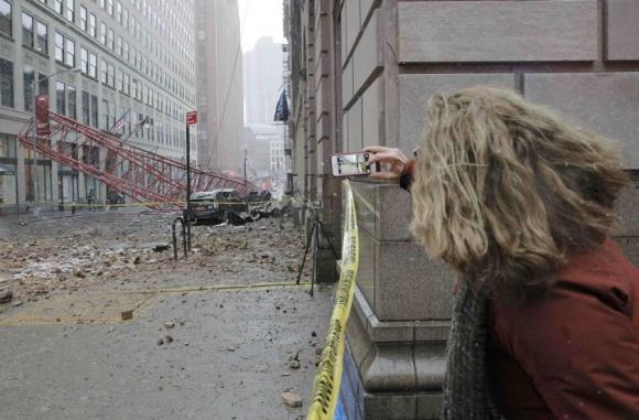 Una mujer le saca una foto a la grúa caída en Nueva York. Foto: Reuters