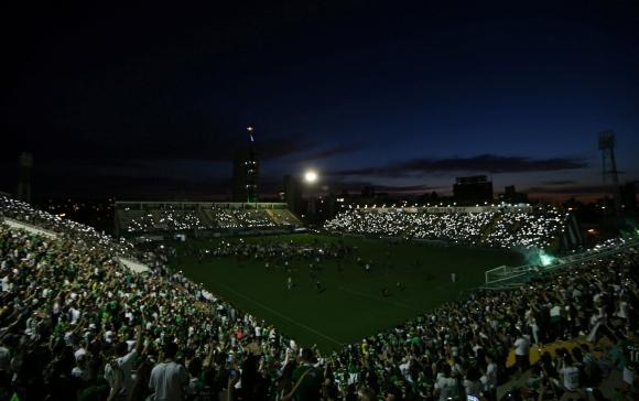 El homenaje de los hinchas de Chapecoense a los fallecidos en el accidente. Fotos: AFP y Reuters