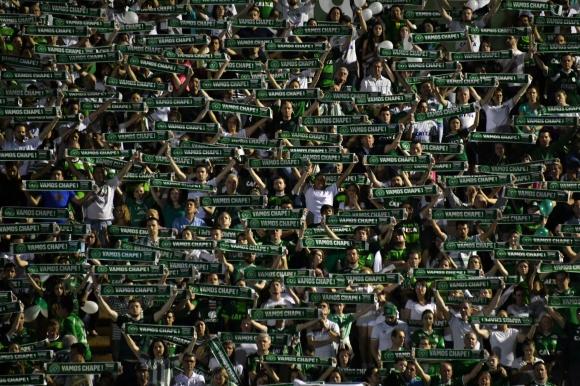 El homenaje de los hinchas del Chapecoense a los jugadores fallecidos en el accidente. Fotos: AFP y Reuters
