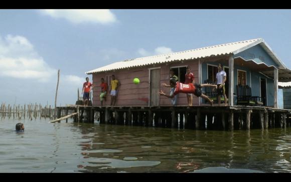 En la aldea de Nueva Venecia, los niños desafían al agua para jugar al fútbol.