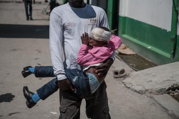 Un padre carga a su hija en un hospital tras el paso del huracán. Foto: EFE