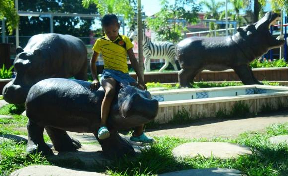 Un niño juega con la estatua de un hipopótamo en Doradal, Colombia. Foto: AFP.