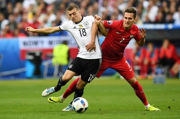 Kroos y Milik disputan el balón. Foto: AFP