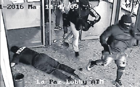 Los delincuentes ingresaron con mucha violencia al BROU y golpearon al guardia en la cabeza. Foto: Captura.
