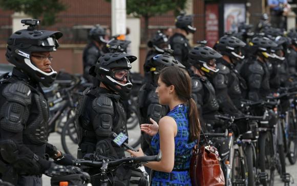 Una periodista de televisión habla con policías desplegados en Cleveland. Foto: Reuters