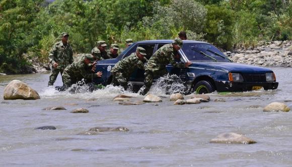 Militares venezolanos empujan un coche abandonado por los colombianos. Foto: AFP