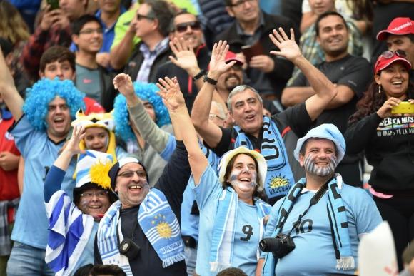 Hinchas de la celeste alentando a la selección en Antofagasta. Fotos: AFP/Reuters.