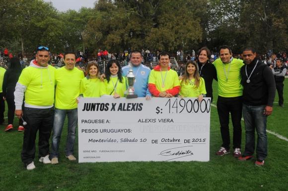 Familiares de Alexis Viera y miembros de la organización con el cheque. Foto: Ariel Colmegna.